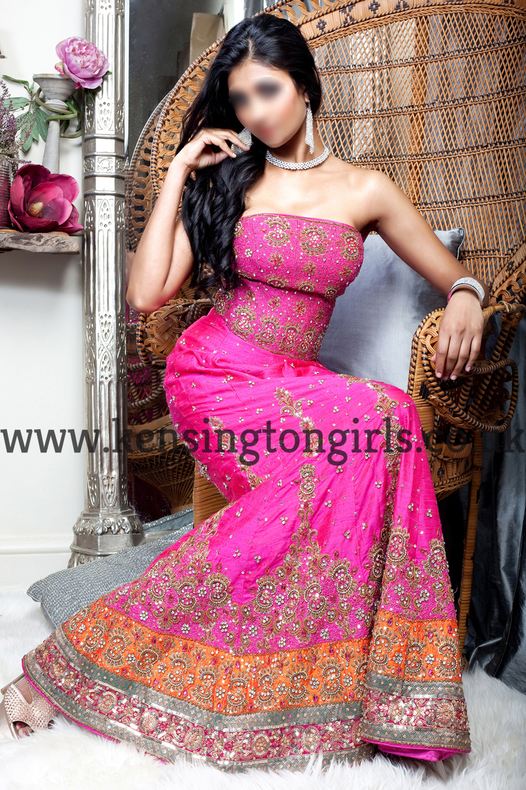 Ria dressed in a full Indian pink exotic gown as she sits on a white chair.